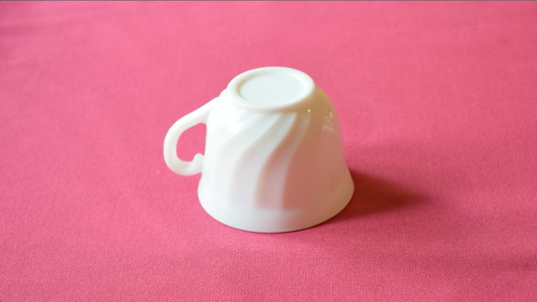 机の上に逆さに置かれたマグカップ