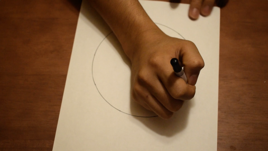 紙を回して握ったペンの先を紙に軽く置いて円を描く