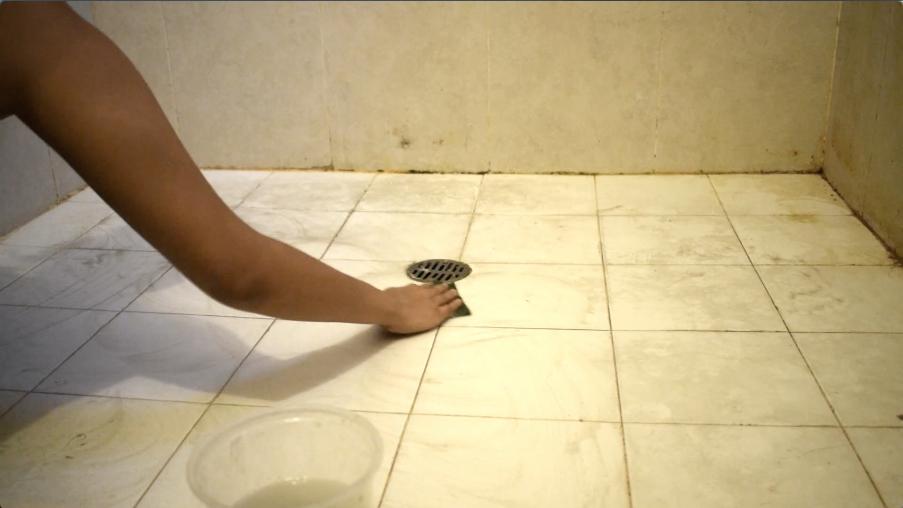 スポンジで床をこすって汚れを落とす