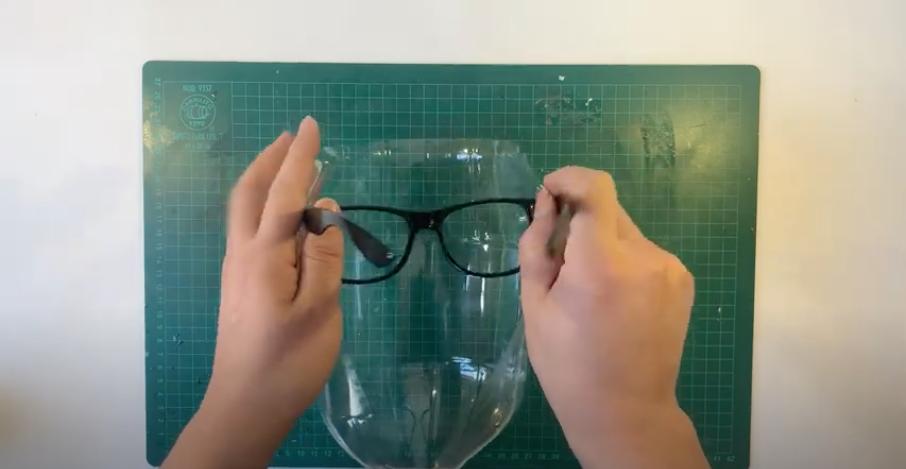 入れた切り込みに沿ってメガネのフレームを通す