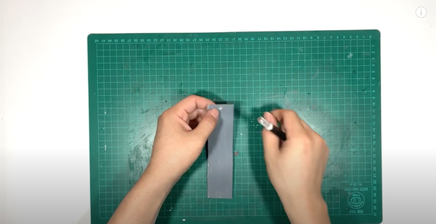 色を塗った厚紙の端に毛糸を通す穴を開ける